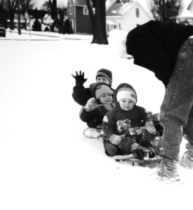 A father playing in the snow with his 3 sons.