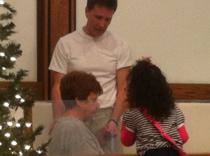 A granddaughter unexpectedly walking up to watch her grandmother be baptized.
